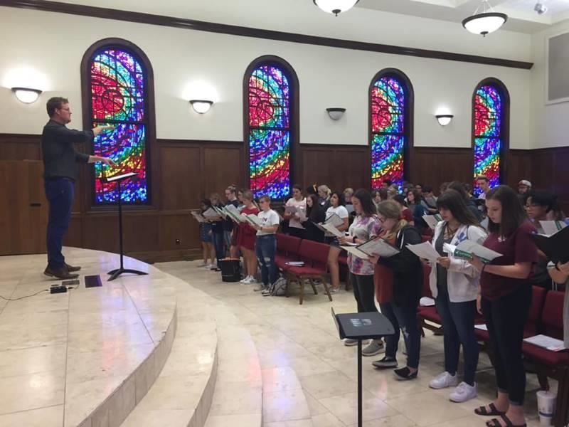 Dr. Chris Rosborough, Director of Choral Activities at HPU, leading the students