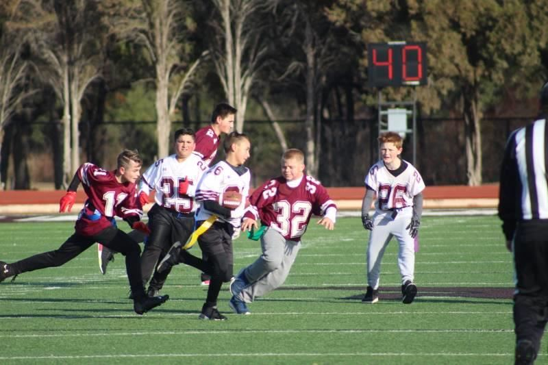 Above: Thomas Franqui dodges other players as he runs the ball during the CIS 6th Grade Flag Football Super Bowl.